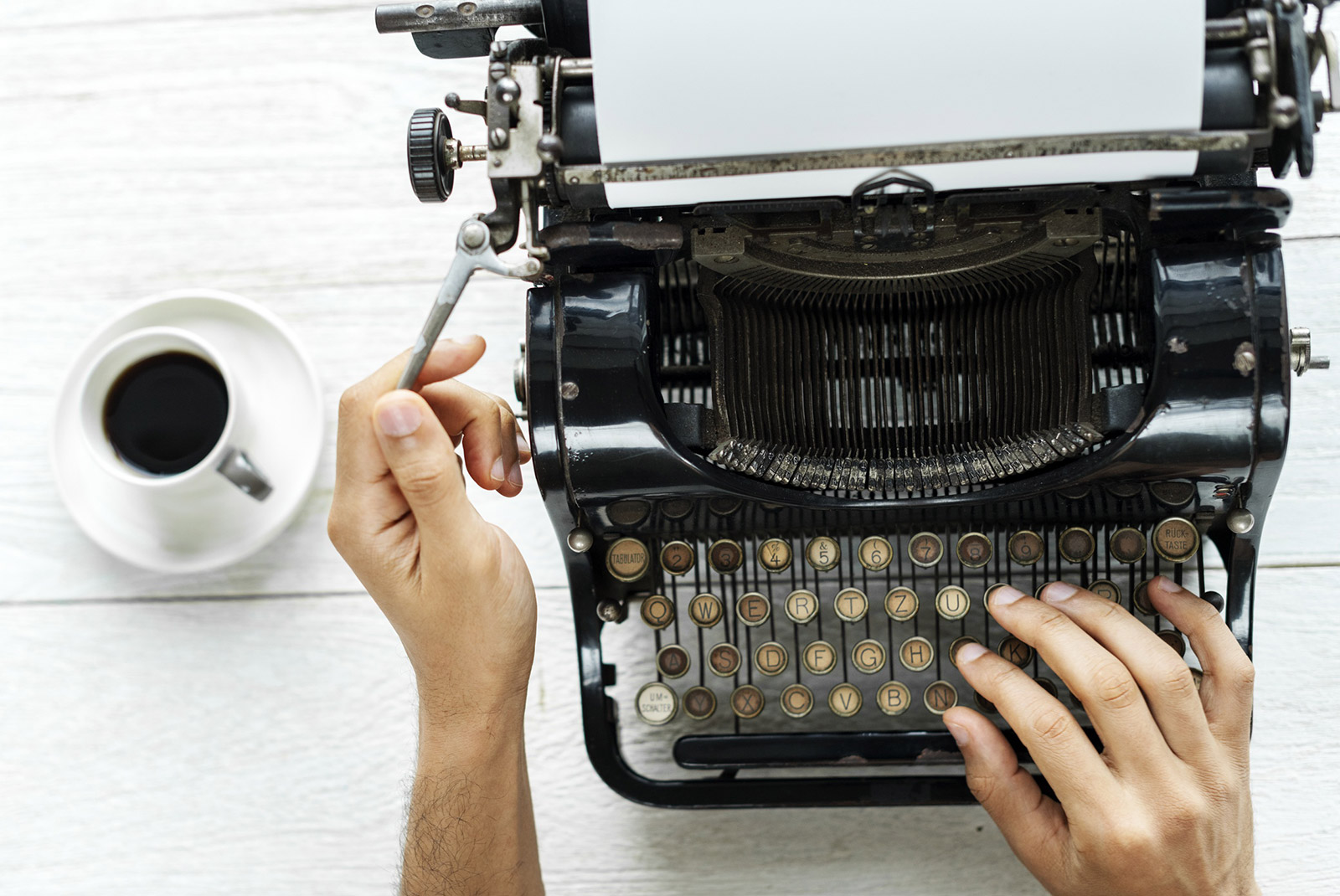 Person using typewriter with a cup of coffee to the side